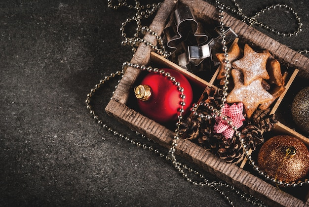 Рождество, новогодние праздничные украшения. елочные шары, гирлянда, пряничные звезды, печенье, плесень, бантики для подарков, еловые шишки в деревянной коробке на черном каменном столе, вид сверху copyspace