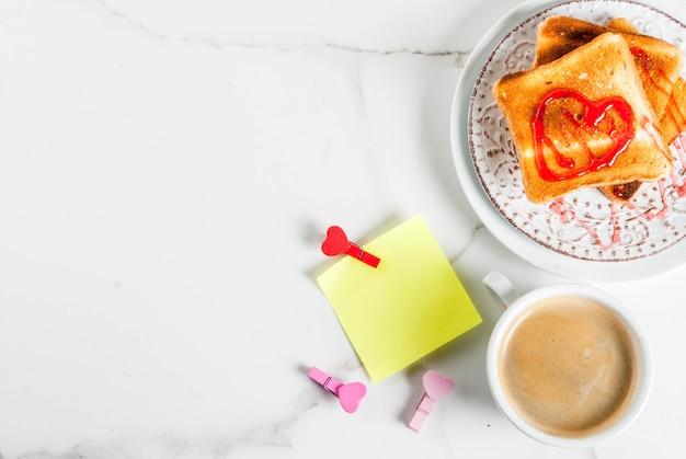 Идея завтрака в день святого валентина с кружкой кофе, поджаренным хлебом с красным клубничным джемом, записка для поздравления с булавками в форме сердца, белый мрамор, вид сверху copyspace