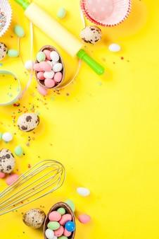 Сладкая выпечка на пасху, приготовление с выпечкой - со скалкой, венчиком для взбивания, формочками для печенья, перепелиными яйцами, посыпкой сахаром. ярко-желтый фон, вид сверху copyspace