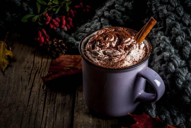 秋の飲み物、ホットチョコレートまたはココアとホイップクリームとスパイス(シナモン、アニス)、古い素朴な木製のテーブル、暖かい居心地の良い毛布、干し草ベリーと葉copyspace