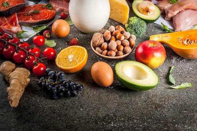 健康的なダイエット 。有機食材、スーパーフード:牛肉と豚肉、鶏肉の切り身、サケの魚、豆、ナッツ、牛乳、卵、果物、野菜。黒い石のテーブル、copyspace