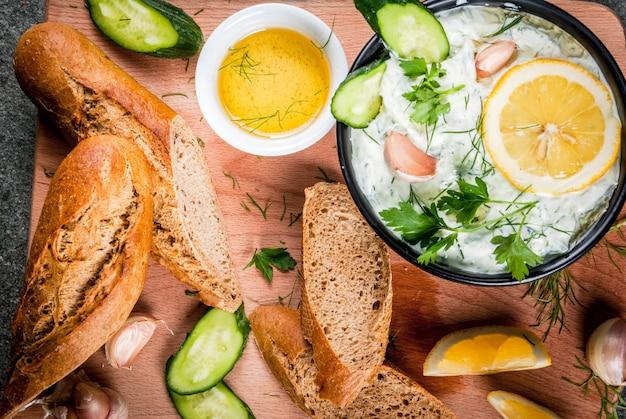 Традиционная кавказская и греческая еда. соус цацики с ингредиентами - огурец, лимон, петрушка, укроп, чеснок. на темном каменном столе. с бутербродами и багетом. вид сверху copyspace