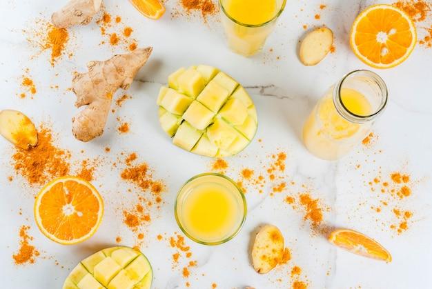 インド料理のレシピ。健康食品、デトックス水。白い大理石のテーブルの上の伝統的なインドのマンゴー、オレンジ、ターメリック、ジンジャーのスムージー。 copyspaceトップビュー