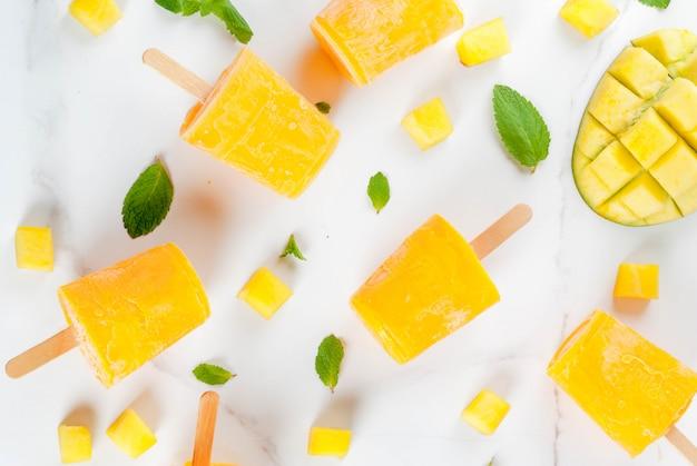 アイスクリーム、アイスキャンディー。オーガニック食材、デザート。白い大理石のテーブルの上にミントの葉とフレッシュマンゴーフルーツを添えた冷凍マンゴースムージー。 copyspaceトップビュー