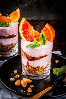 健康的な朝食、グラノーラとブラッドオレンジパフェ。ヨーグルト、アーモンドとミント、濃いさびた、copyspace