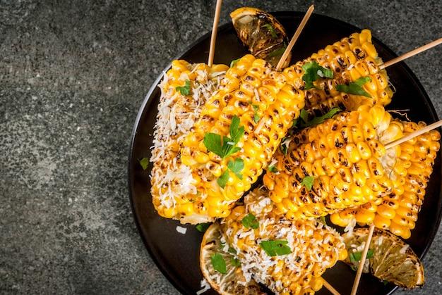 Летняя еда. идеи для барбекю и гриль вечеринок. жареная кукуруза на гриле в огне. с посыпать сыром (элотес), острым перцем чили, лимоном. на темном каменном столе, черная тарелка copyspace вид сверху