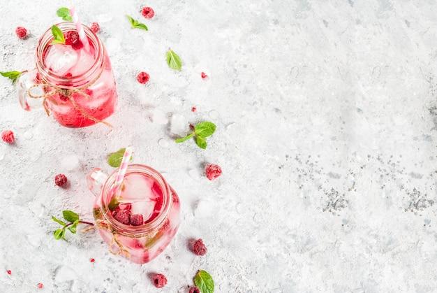 冷たい夏の飲み物、ラズベリーサングリア、レモネードまたはモヒート、新鮮なラズベリーとシロップ、ミントの葉、灰色の石copyspaceトップビュー