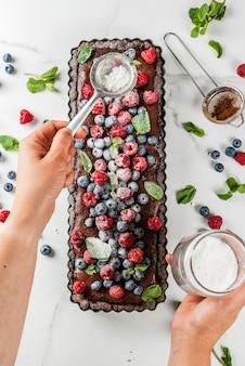 Летняя домашняя выпечка. пирог шоколадный торт с шоколадным кремом, черника малина, листья мяты, женщина посыпать сахарной пудрой. белый мраморный стол, близкий вид сверху copyspace руки