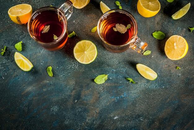 Черный чай с лимоном и мятой на темно-синем бетонном камне, вид сверху copyspace