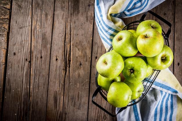 ブラックメタルバスケット、古い素朴な木製、copyspaceトップビューで新鮮な生有機農場緑のリンゴ