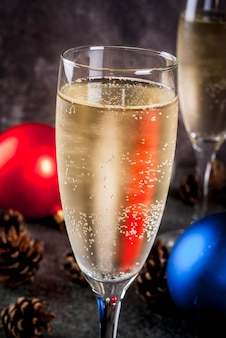 Сухое шампанское в бокалах, разноцветные елочные шары, сосновые шишки, новогодний натюрморт на темном камне, селективный фокус copyspace