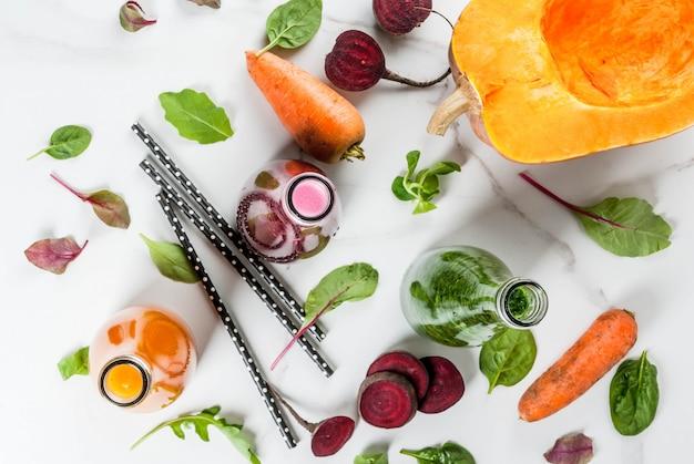 ビーガンダイエット食品。カラフルな新鮮な有機スムージーの選択は、秋野菜と一緒に飲みます:ビートルート、カボチャ、ニンジン、葉物野菜。ボトル、白いテーブル。 copyspaceトップビュー