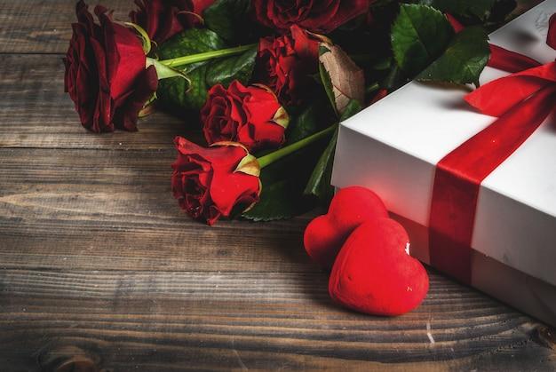 休日、バレンタインデー。赤いバラの花束、赤いリボンとネクタイ、ラップされたギフトボックス。木製のテーブル、copyspace