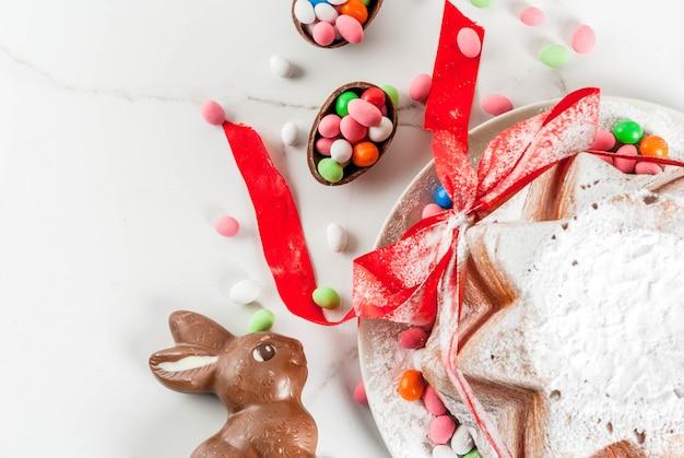 伝統的なイタリアのフルーツケーキパネトーネパンドーロ、お祝いの赤いリボン、イースターのウサギ、甘いお菓子の卵の装飾、木製の家、copyspaceトップビュー