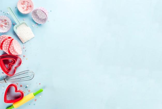 Сладкая выпечка на день святого валентина, приготовление с выпечкой на скалке, венчик для взбивания, формочки для печенья, сахарная посыпка, мука. голубой, вид сверху copyspace