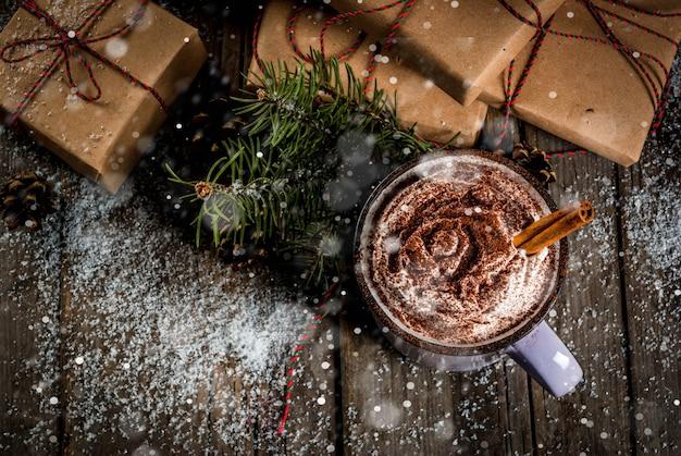 Рождество, горячий шоколад или какао со взбитыми сливками и специями, рождественские подарки, леденцы, ветка рождественской елки, сосновые шишки, старый деревенский деревянный стол со снегом, вид сверху copyspace тонированное