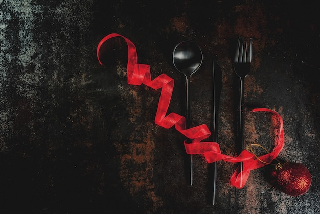 Рождество, концепция празднования нового года, набор столового серебра на темном ржавом, украшенный красной лентой и елкой мяч, вид сверху copyspace
