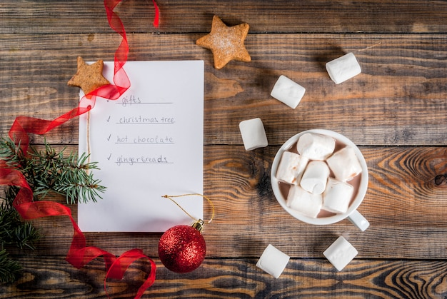 クリスマス、新年のコンセプト。木製テーブル、リストを行うためのノート、ジンジャーブレッド、ギフト、ホットチョコレート、クリスマスツリー、ココアマグカップ、クリスマスボール、松の木、赤いリボン、マシュマロ。トップビューcopyspace