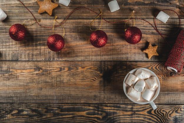 Празднование рождества, нового года. деревянный стол с украшениями, праздничная веревка, елочные шары, зефир, чашка горячего шоколада, вид сверху copyspace