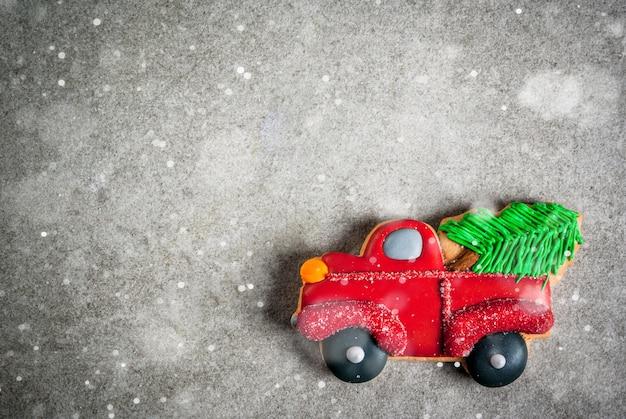 灰色の石のテーブルの上にクリスマスツリーが付いている車の形でクリスマスの手作りのカラフルなジンジャーブレッドクッキー。トップビュー、copyspace