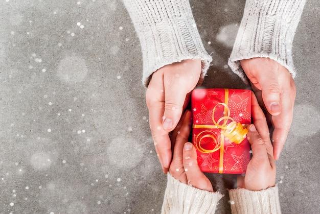 休日、クリスマスの準備。写真の女性と男性の手は、暖かいセーターを着て、金色のリボンが付いた赤い包装紙で贈り物を持ちます。灰色、雪の効果、トップビューcopyspace