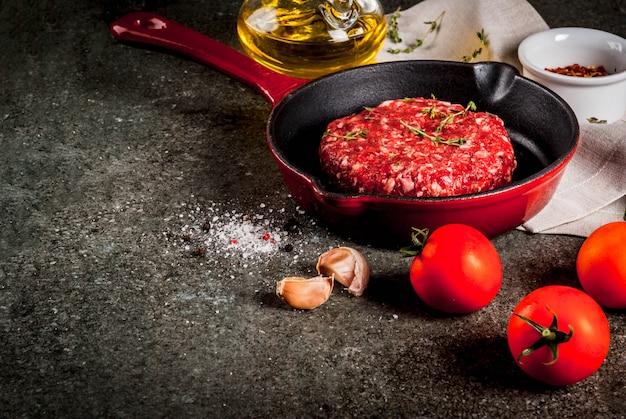 黒、copyspaceのフライパンでスパイス、タイム、トマト、オリーブオイルと生の有機牛肉ハンバーガーカツレツ