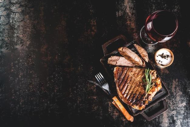 グリル鍋ボードにスパイスと牛肉のグリルステーキ、赤ワイングラス。 copyspaceトップビュー