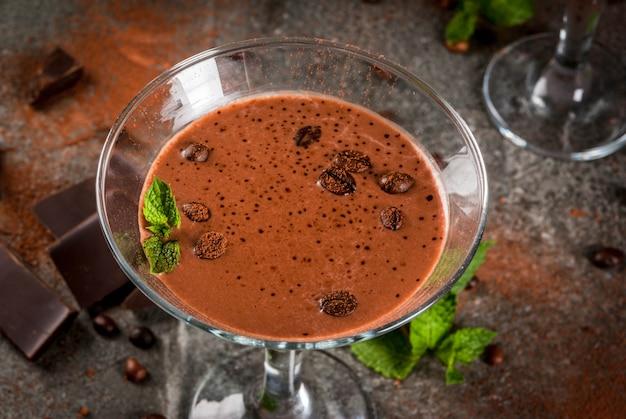 Кофейный крем-кофе, шоколадный мартини с мятой на черном каменном столе, copyspace