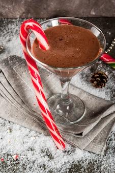 Рождественские напитки, коктейль из мятного мокко и мартини с конфетой, на сером copyspace