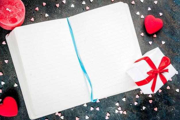 バレンタインコンセプト、メモ帳、ペン、装飾的な甘い心、赤いろうそくでお祝いの言葉。トップビューcopyspace