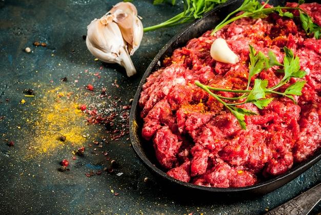 暗いテーブル、copyspaceにスパイスと新鮮なハーブとひき肉