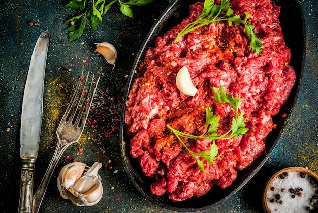 スパイスと暗いテーブル、copyspaceトップビューで新鮮なハーブとひき肉