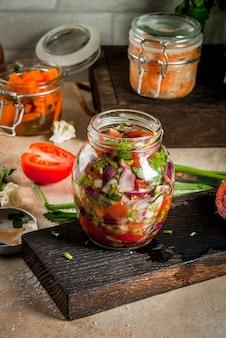 Понятие о ферментированной еде. домашние консервы и заготовки. веганская еда. овощи. банки консервированной сальсы, квашеной капусты, маринованной моркови, кимчи и цветной капусты брокколи. домашний кухонный стол. copyspace