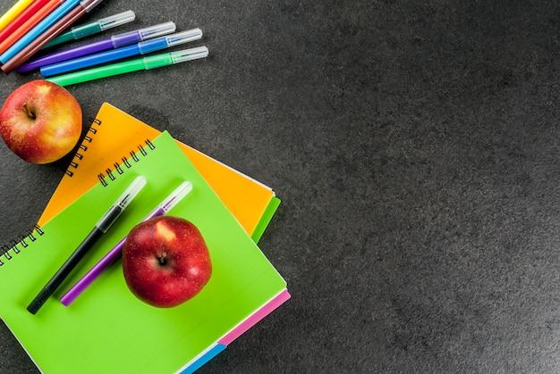 Обратно в школу. фрукты яблоки с тетрадями, цветные ручки на черном столе. copyspace вид сверху