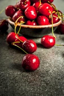 Свежие сырые органические сезонные фрукты. вишня с каплями воды на темном каменном столе. copyspace