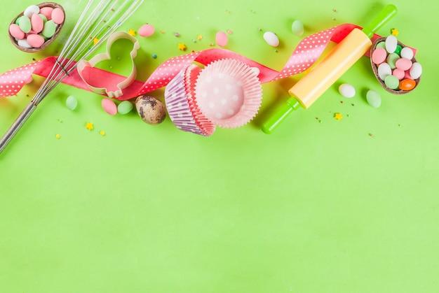 Концепция сладкой выпечки на пасху, приготовление с выпечкой - со скалкой, венчиком для взбивания, формочками для печенья, сахарной посыпкой, мукой. светло-зеленый, вид сверху copyspace