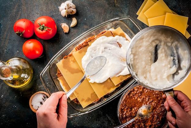 暗い青色のテーブルの上の自家製の古典的なラザニアボロネーゼを調理する女性。食材、トップビューcopyspace、画像の手で