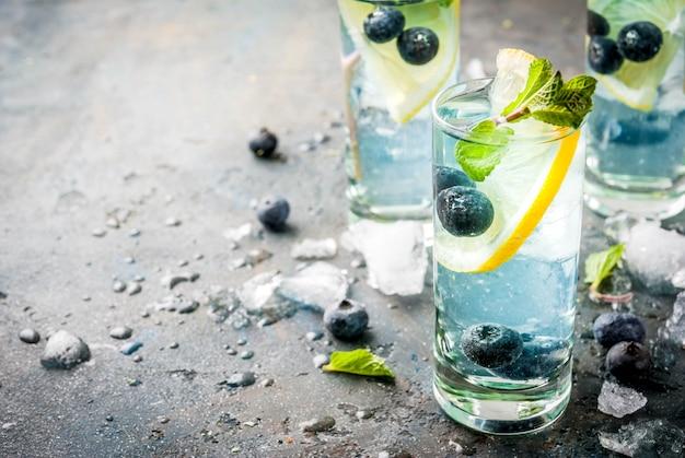 夏の飲み物、ブルーベリーレモネードまたはモヒートカクテル、レモン、フレッシュブルーベリーとミント、ダークブルーストーンcopyspace