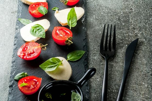 イタリアの夕食。自家製サラダカプレーゼ-トマト、新鮮なバジル、モッツァレラチーズ、オリーブオイル。黒い石のテーブルの上。串焼きを添えて。 copyspaceトップビュー