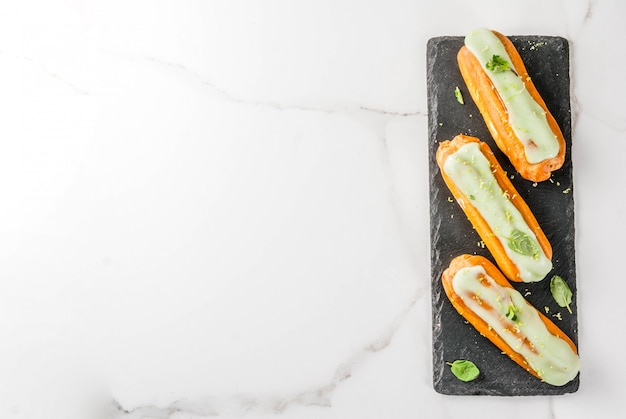 伝統的なフランスのデザート。ライムの皮とミントの葉とモヒートエクレア、濃い青、copyspaceトップビュー