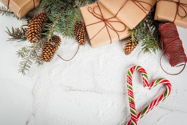 Концепция рождество, ветви елки, сосновые шишки, подарки и традиционные новогодние конфеты конфеты тростника, на белый мраморный стол со снегом. copyspace вид сверху