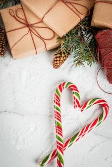 クリスマスの時間の概念、クリスマスツリーの枝、松ぼっくり、ギフト、雪と白い大理石のテーブルの上の伝統的な新年のお菓子キャンディー杖。 copyspaceトップビュー