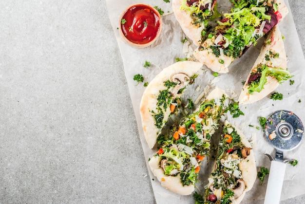 新鮮な野菜とペスト、灰色の石、copyspaceトップビューのビーガンピザ