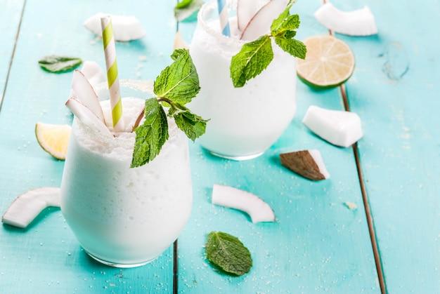 Летние прохладительные напитки, коктейли. замороженный кокосовый мохито с лаймом и мятой. пина колада. на светло синий зеленый деревянный стол с ингредиентами. copyspace