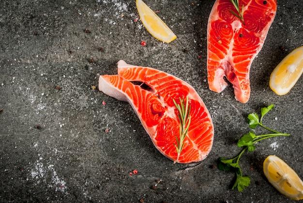 Сырая свежая лососевая рыба с ингредиентами для приготовления пищи - оливковое масло, лимон, лук, петрушка, розмарин, на черном каменном столе, вид сверху copyspace
