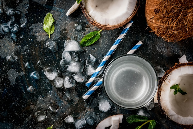健康食品のコンセプト。さびたダークブルー、copyspaceトップビューに、ココナッツ、アイスキューブ、ミントと新鮮な有機ココナッツ水