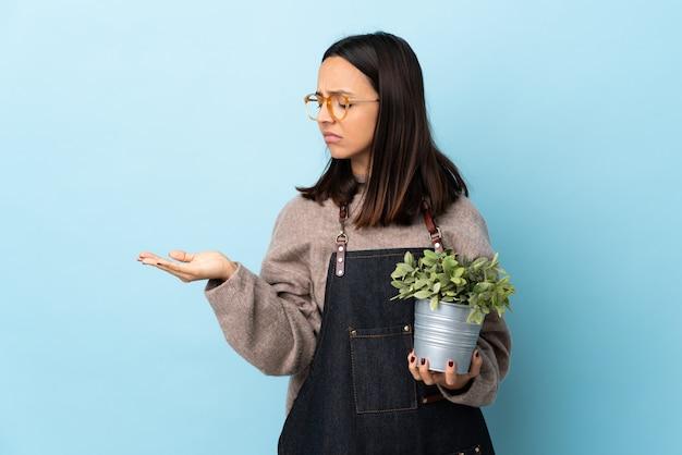 疑問を持つcopyspaceを保持している孤立した青い空間に植物を保持している若いブルネット混血女性