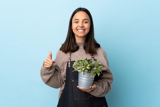 広告を挿入するために手のひらにcopyspaceの架空の部分を保持している孤立した青い空間の上に植物を保持している若いブルネットの混血女性と親指