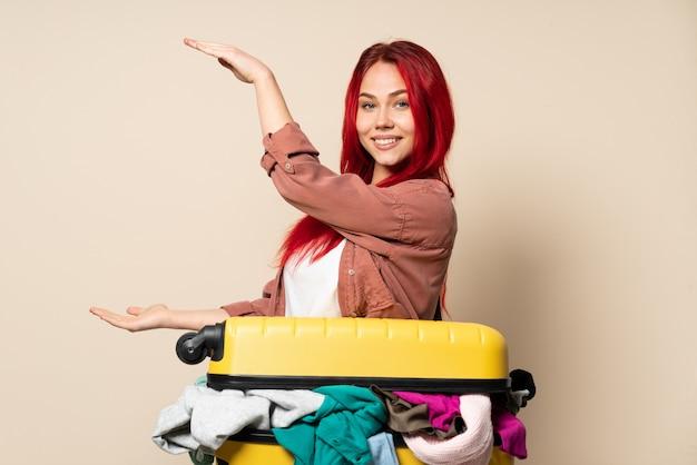 広告を挿入するcopyspaceを保持しているベージュの壁に分離された服の完全なスーツケースを持つ旅行者女性