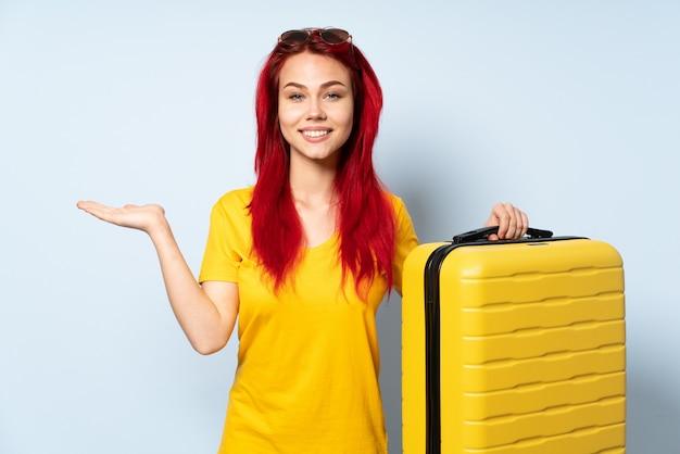 広告を挿入する手のひらに空のcopyspaceを保持している青い壁に分離されたスーツケースを保持している旅行者女性